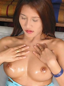 Busty thai spreads her wet asian pussy and plugs a big dildo in it