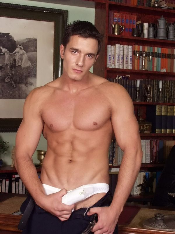 Muscular gay stud strips off
