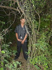 Latino greasing his pole while under the wild vines