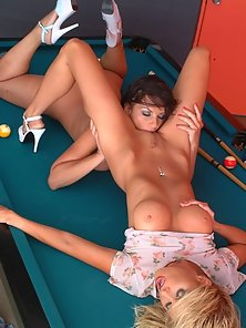 Blonde and brunette lesbians lustfully licking each other on top of the pool table