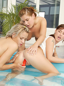 Two teen girls catching another girl in the swimming pool