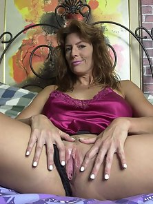 Brunette mother poking herself with purple dildo