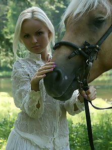 Pretty blonde riding horse naked in woods