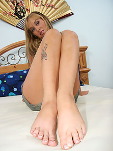 Blonde tattoed cutie takes a massive load on her feet