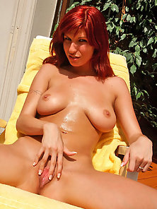 Redhead Tara shows off her big tits and nice ass
