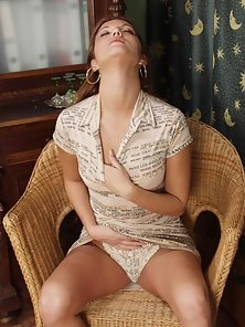 Sexy brunette strips and spreads on the chair