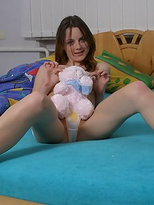 Busty young looking Mila is awakining and playing nude with her light-blue teddy-bear.