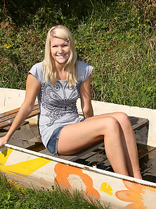 Teenage blonde in a stranded boat