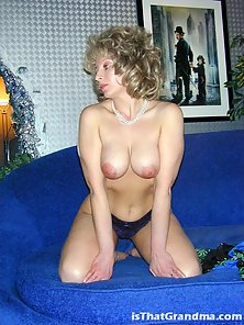 Curly grandma Laura touching her boobs on the sofa