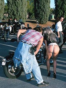 Huge boobed blonde posing nude on a bike