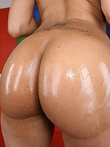 Sexy mocha skinned hottie oils up her round ass in these