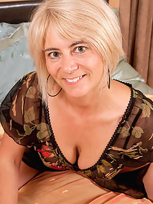 Anilos Dana boasts a pair of huge tits and fingers her mature pussy in her bedroom