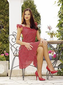 Evelyn Lory spreading her long legs in red polka dress